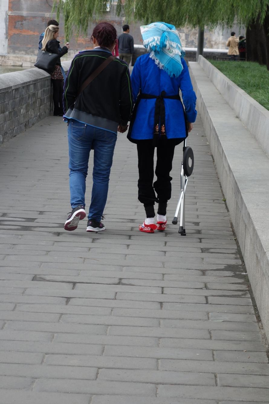 Woman with bound feet walking near Forbidden City. Fascinating yet also disturbing...