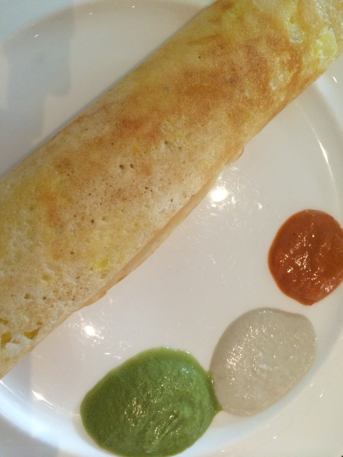Breakfast South India style - dosa is a thin pancake stuffed with potato and served with coconut, coriander or tomato chutne